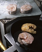 Tuna steaks being fried in a pan