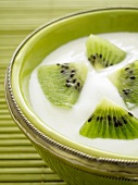 Natural yogurt with kiwis in a green bowl (close-up)