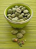 Wasabi-Erdnüsse in grüner Schale auf Bambusmatte