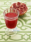 A glass of pomegranate juice with half a pomegranate in the background