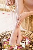 Frau begiesst ihre Beine mit Massageöl