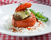 A tomato stuffed with mincemeat and cheese on a bed rice
