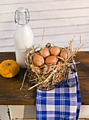 Fresh eggs in a wire basket, a pumpkin and a bottle of milk