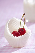 Fresh cherries in unused paper cases for muffins