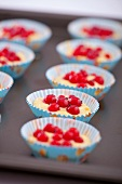 Unbaked redcurrant muffins on a baking tray