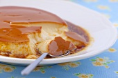 A plate of creme caramel with a spoon (close-up)