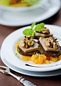 Foie gras with walnuts and pumpernickel on orange salad