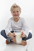 A little boy holding a glass of milk