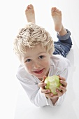 A little boy holding a half eaten apple