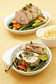 Turkey roulade with herb cheese and pea stuffing on vegetables