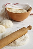 Dough with rolling pin and in bowl half-covered by tea towel