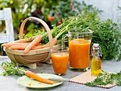 Möhrensaft und frische Möhren auf Gartentisch