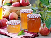 Jars of apple jelly, fresh apples