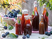 Plum juice in bottles, fresh plums in basket
