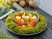 Wreath of fennel flowers around burning candles in glass