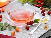 Cup of rose hip tea, sugar crystals in spoon, rose hips