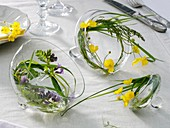 Kleine Kränze aus Gräsern und Blumen in Glasdeckeln
