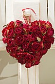 Herz aus getrockneten roten Rosenblüten an Türknauf