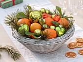 Weihnachtlicher Korb mit Orangen und Kieferzweigen