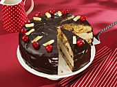 Banana cake with chocolate icing and cherries