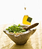 Fresh basil and pine nuts in a marble mortar with a pestle