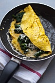 Spinach and Parmesan omelette in frying pan