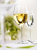 Glass of white wine and glass of water on laid table