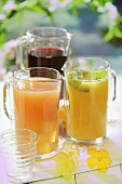 Three different fruit juices in glass jugs