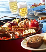 Sausages, vegetable kebabs, turkey rolls, tomato & cevapcici on a barbecue