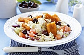 Vegetable salad with fish fingers and olives