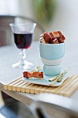 Crispy fried diced bacon and glass of red wine