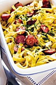 Baked tagliatelle with sliced sausages and Camembert