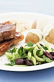 Grilled lamb steaks with Greek salad, potatoes and feta sauce