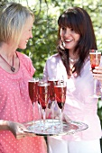 Two women with sparkling wine cocktails out of doors
