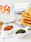 Prawns with ice cubes in glasses, baked filo pastry sheets, salsas