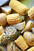 Barbecue vegetables: corn on the cob, potatoes and garlic with herbs