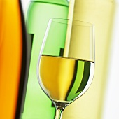 Glass of white wine in front of wine bottles