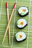 Maki sushi and chopsticks on bamboo mat