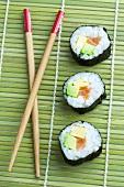 Maki-Sushi und Stäbchen auf Bambusmatte