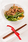 Sweet and sour noodle stir-fry with ham and vegetables