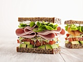 Sliced sausage or salmon and salad sandwiches in whole grain bread