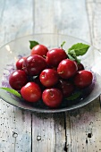 Red plums on glass plate