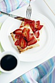 Person eating strawberries on toast with balsamic vinegar