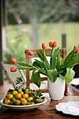 Mandarin oranges and vase of tulips on rustic table