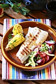 Barbecued fish fillet with corn on the cob and vegetable salad