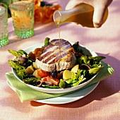 Pouring olive oil over tuna steak on vegetable salad