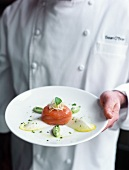 Head chef holding salmon in shape of timbale on a plate
