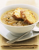 Onion soup with baguette slices topped with toasted cheese