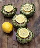 Artichocken mit Zitronenscheiben zum Kochen vorbereitet