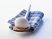 A white egg on a wooden spoon